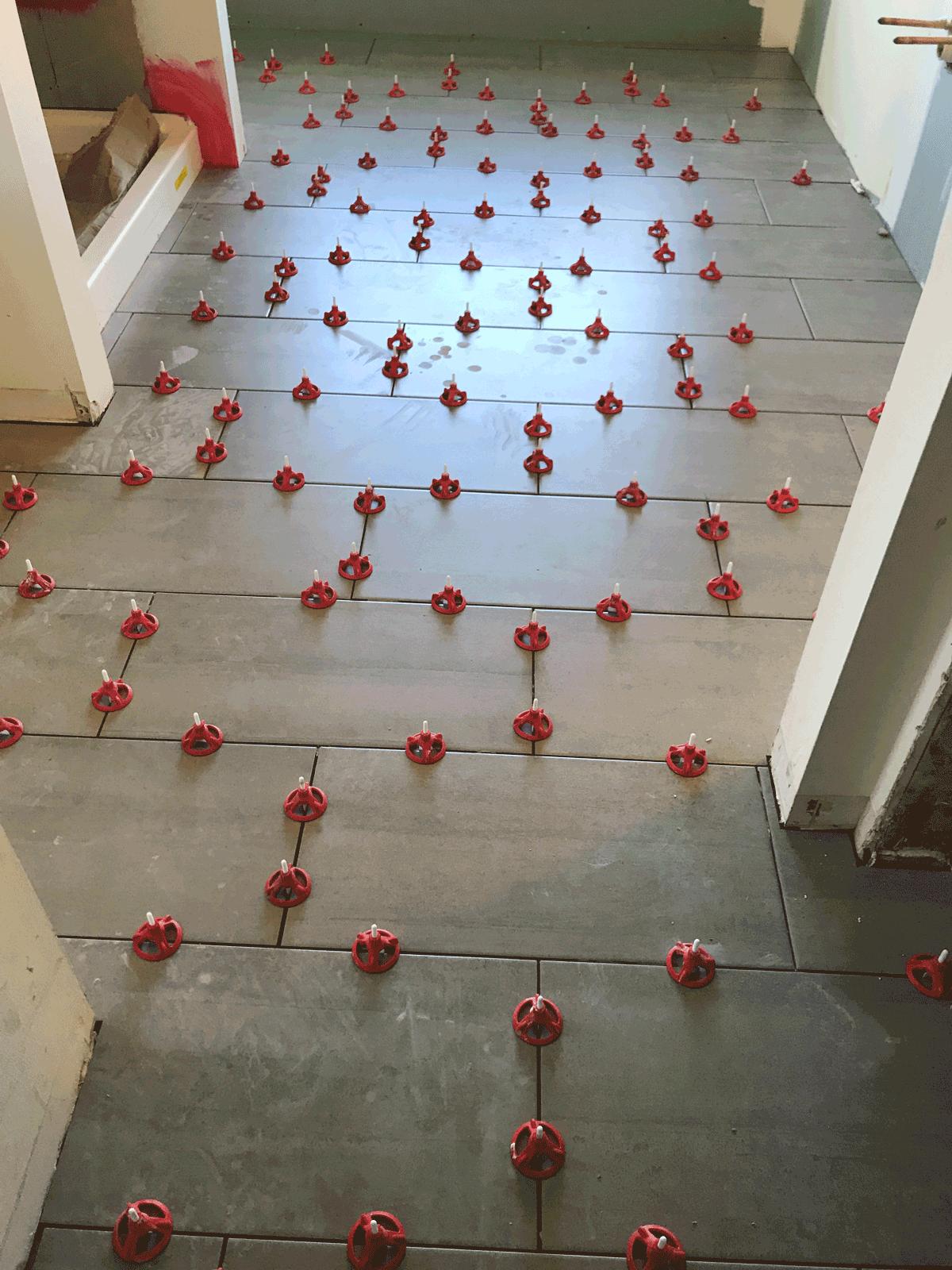 gray floor tile install in a master bathroom renovation