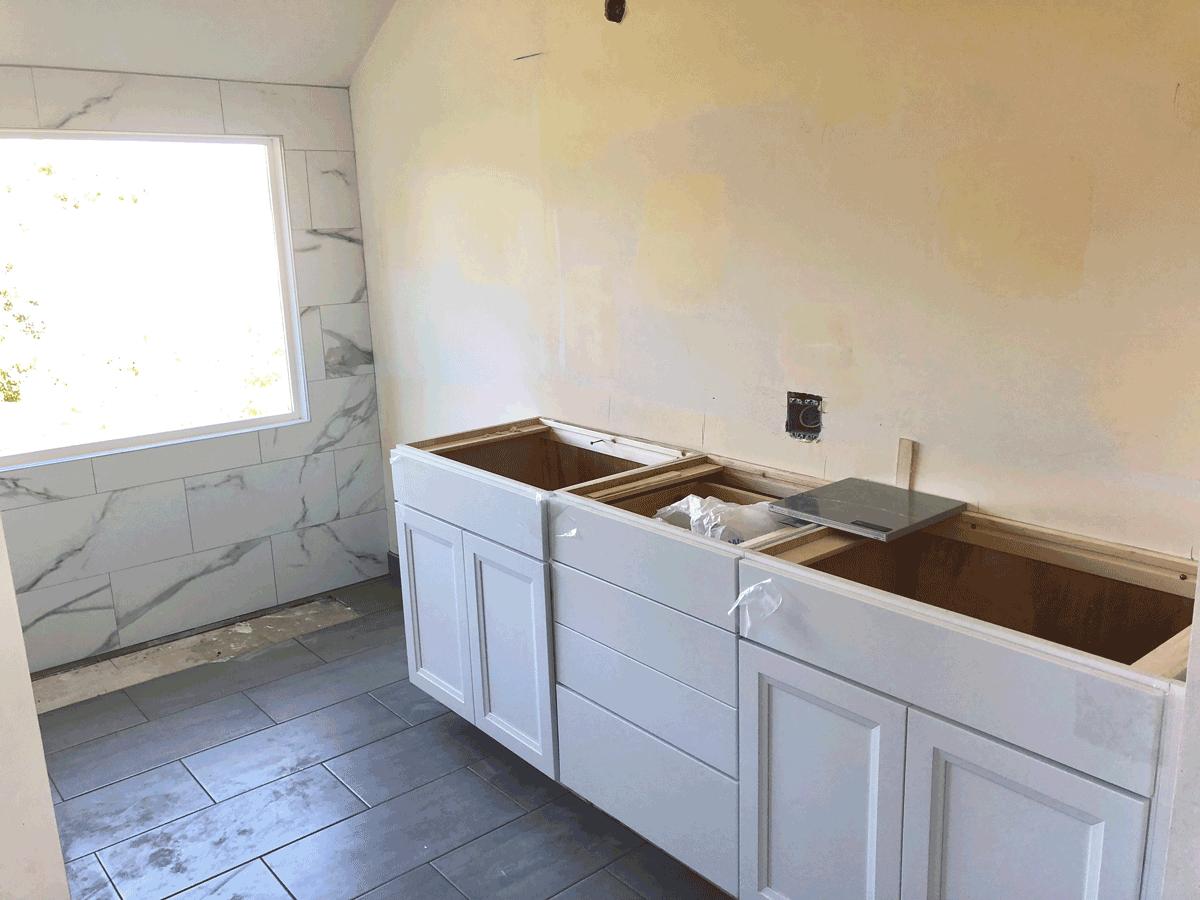 white vanity being installed for master bath reno