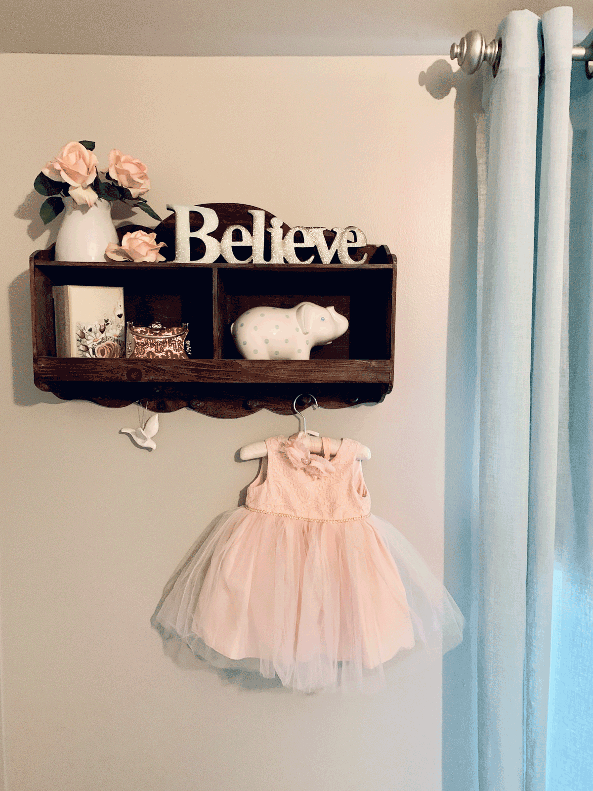 shelf styling for a baby girl's nursery with hanging pink dress