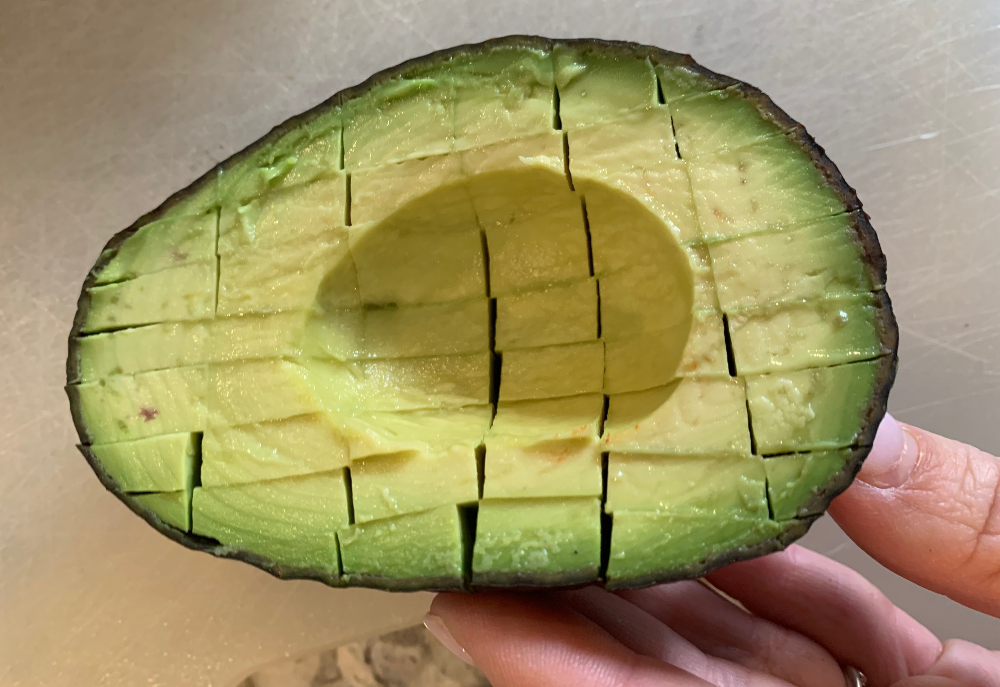 sliced and diced avocado in the skins