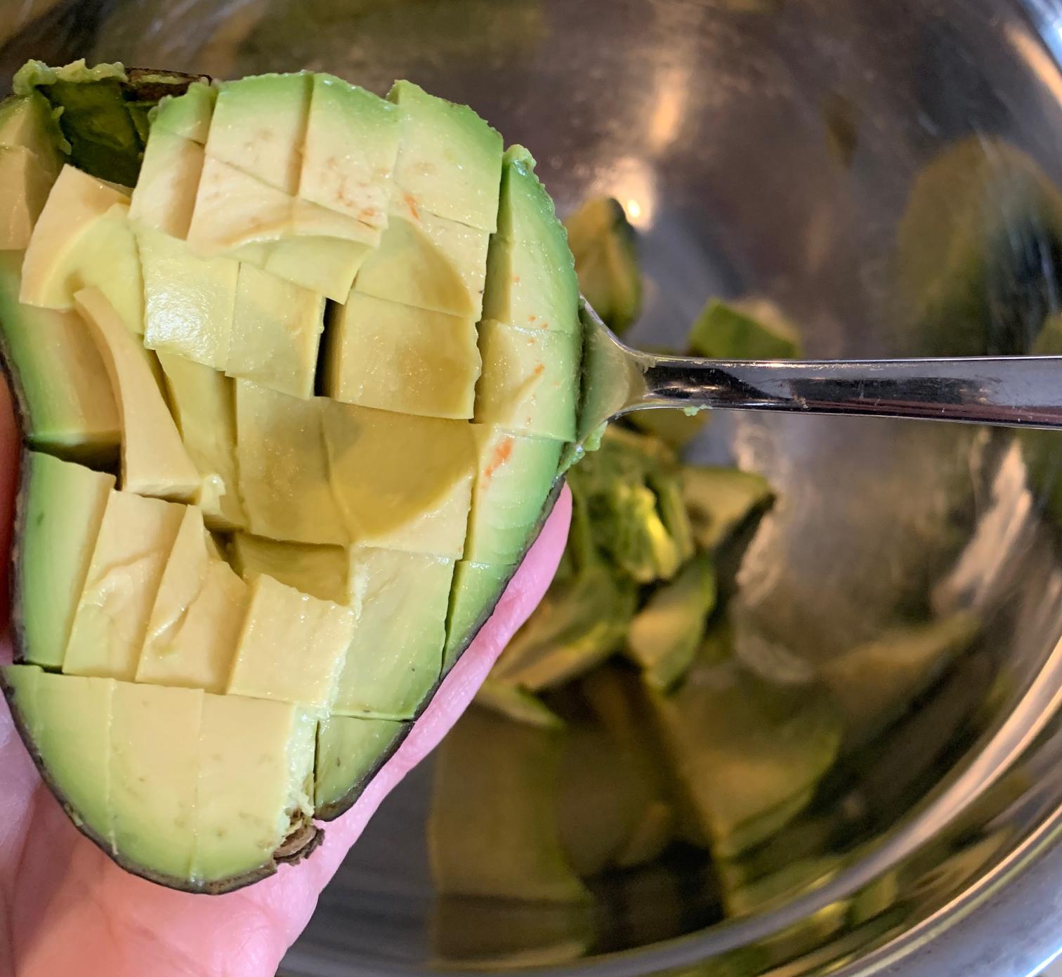 spooning avocado into bowl for guacamole recipe
