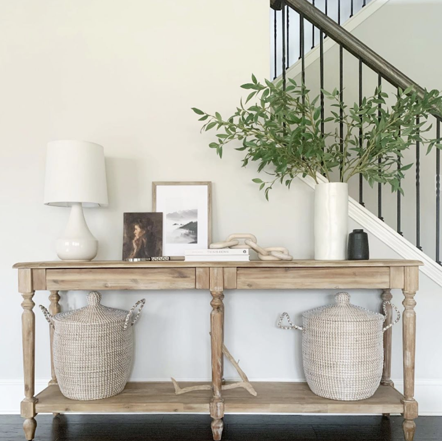 Entryway table with woven baskets white vase with branches