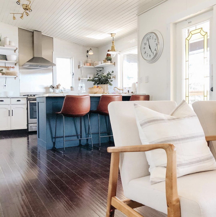 white home with blue kitchen island and camel colored chairs