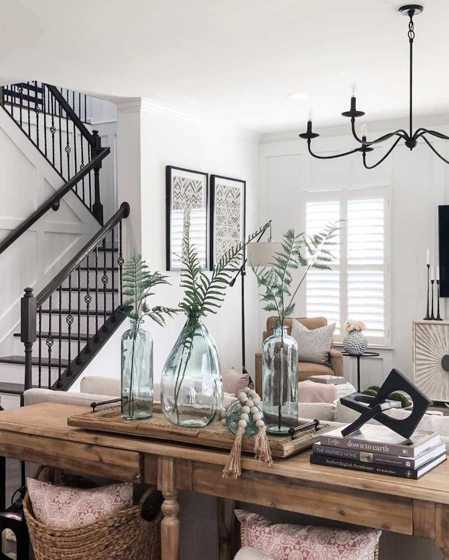 black banister staircase open floor plan living room with ferns in blue glass vases