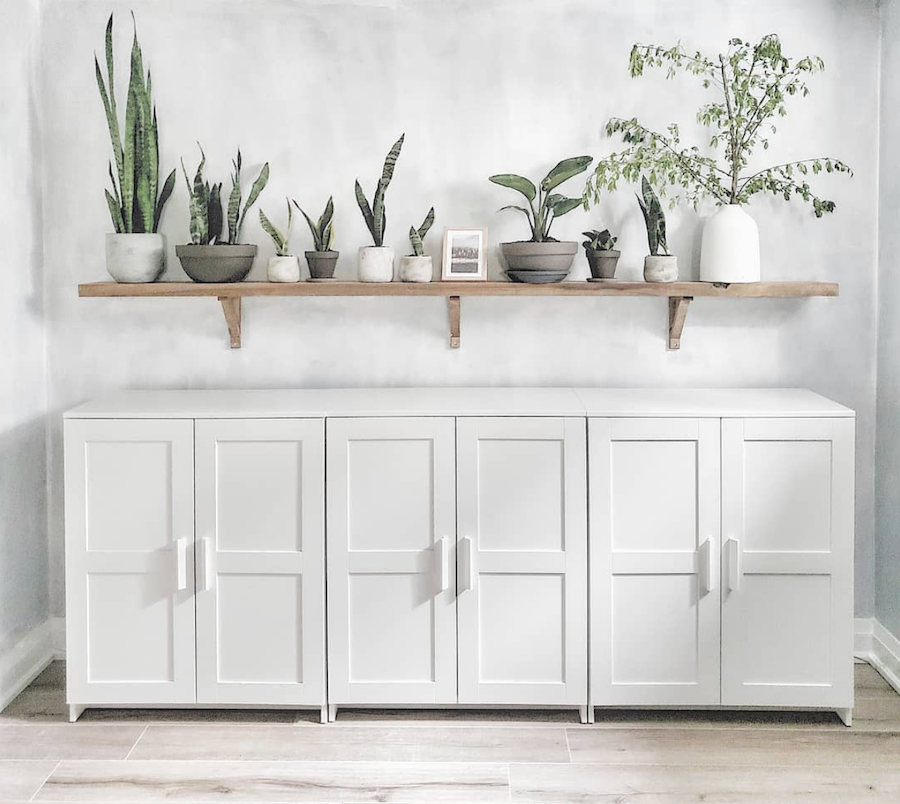 white cabinet with natural wood plant shelf