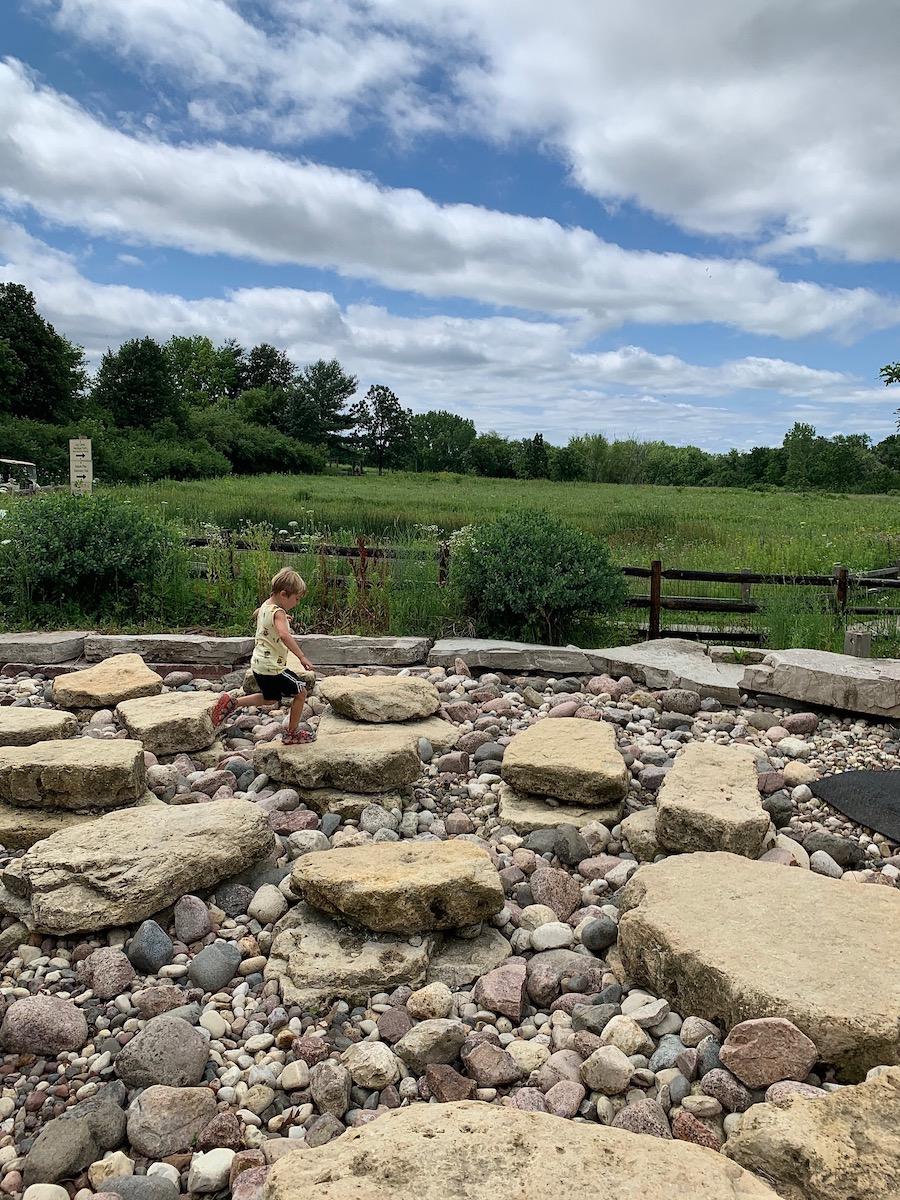 child runs over rocks in nature playground schaumburg il