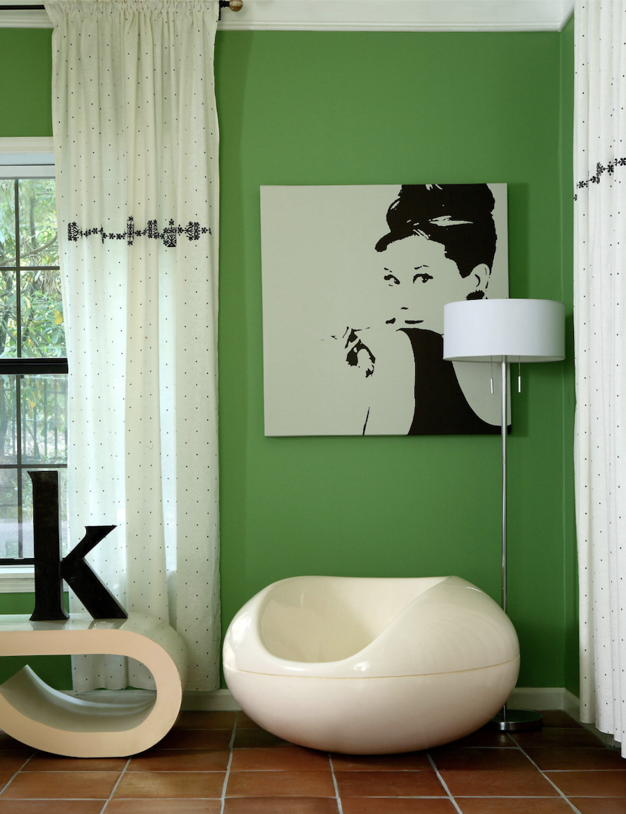 green accent wall in bedroom with audrey hepburn art