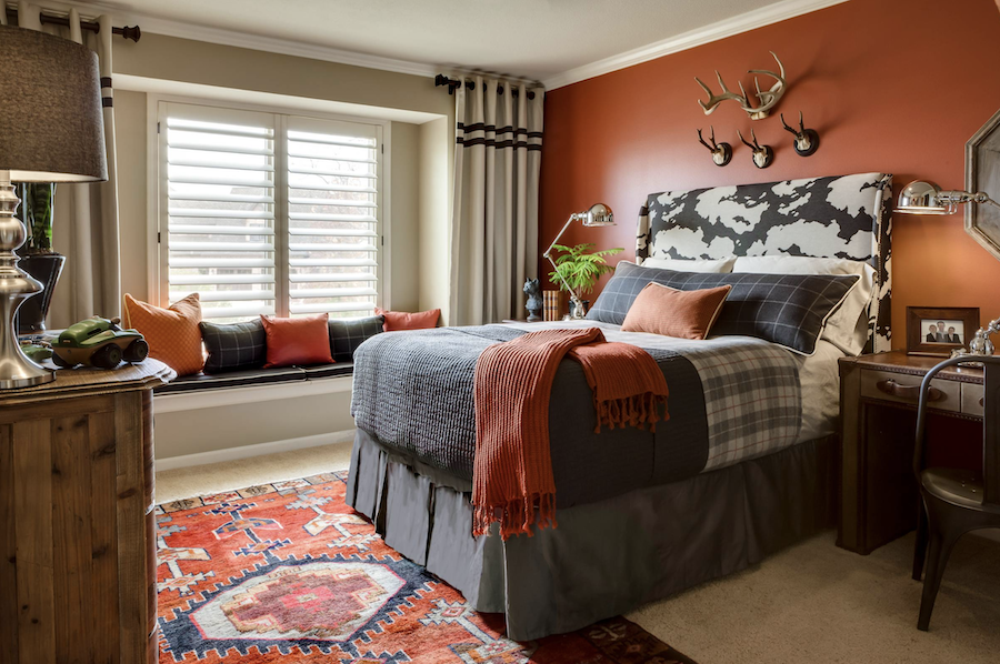 rust colored accent wall in bedroom with antlers on wall