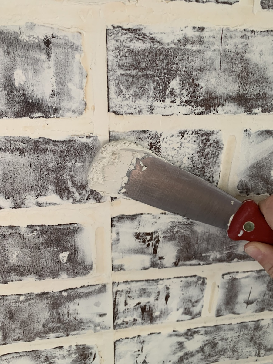 applying joint compound with putty knife to brick wall