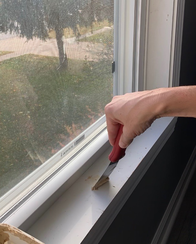 filling nail holes with spackle knife