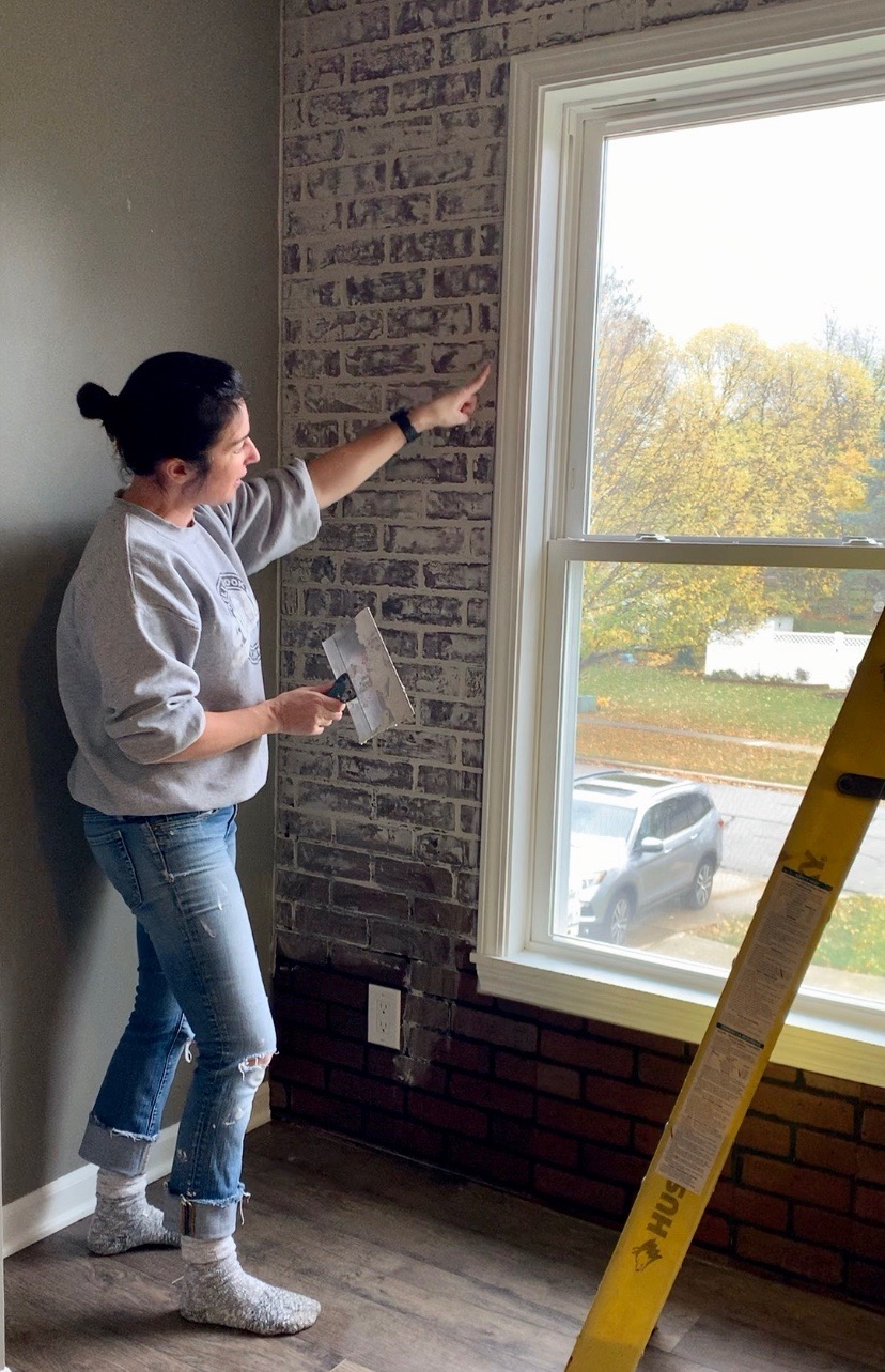 running finger along window frame after adding german schmear to faux brick wall