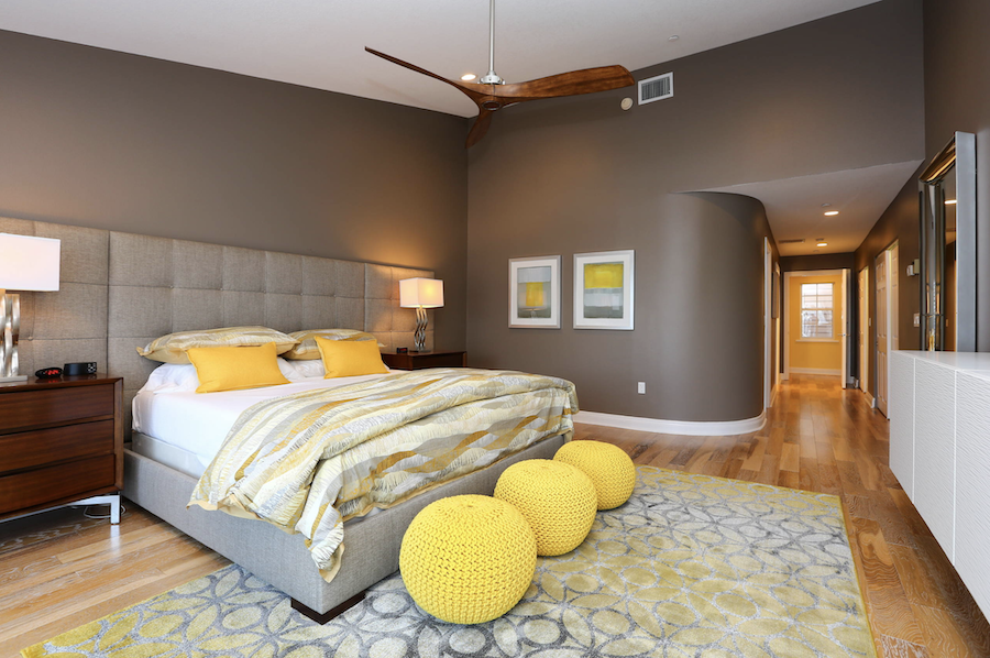greige bedroom with yellow accent pieces