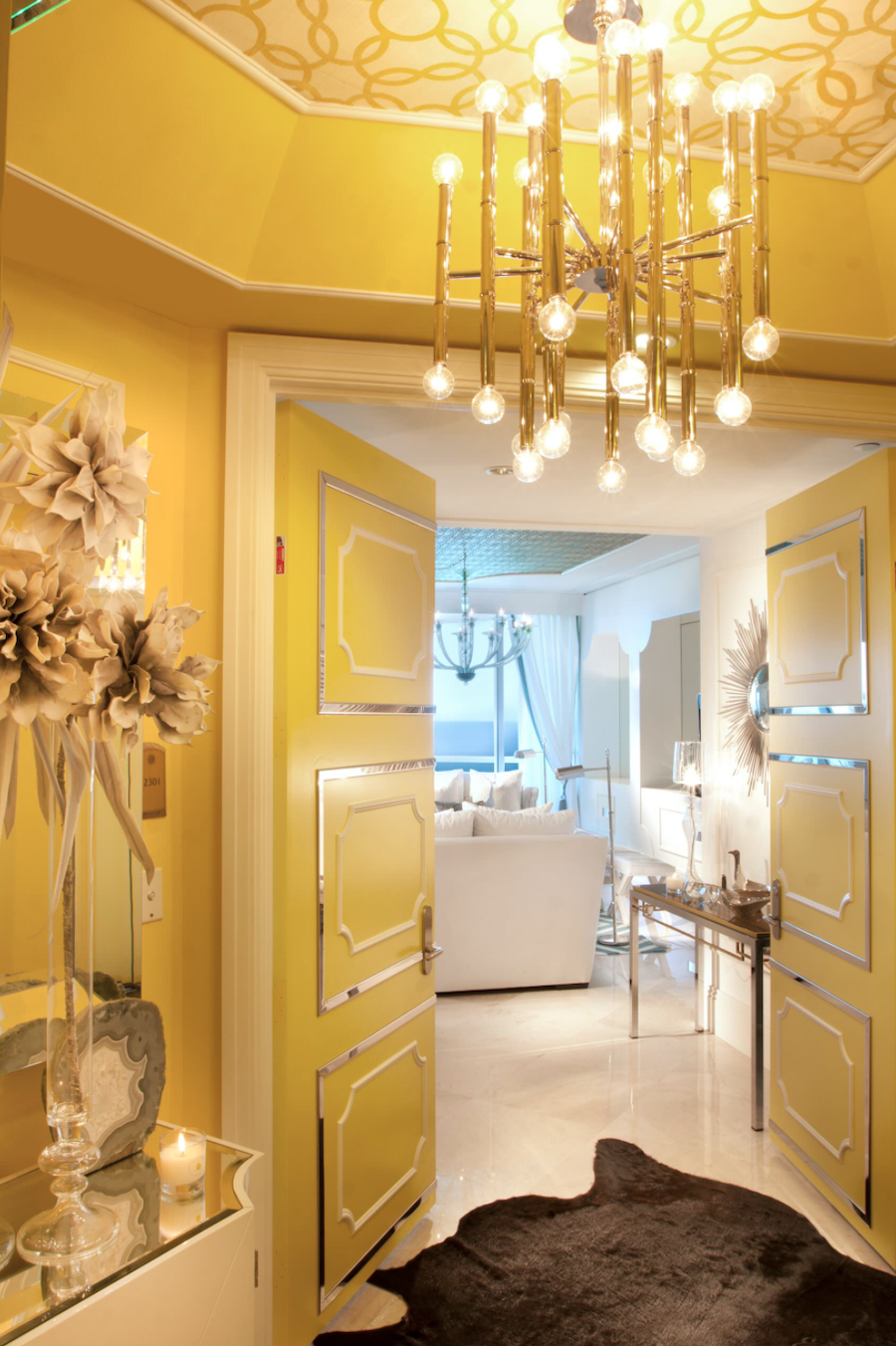 illuminating yellow hallway with patterned wallpaper ceiling