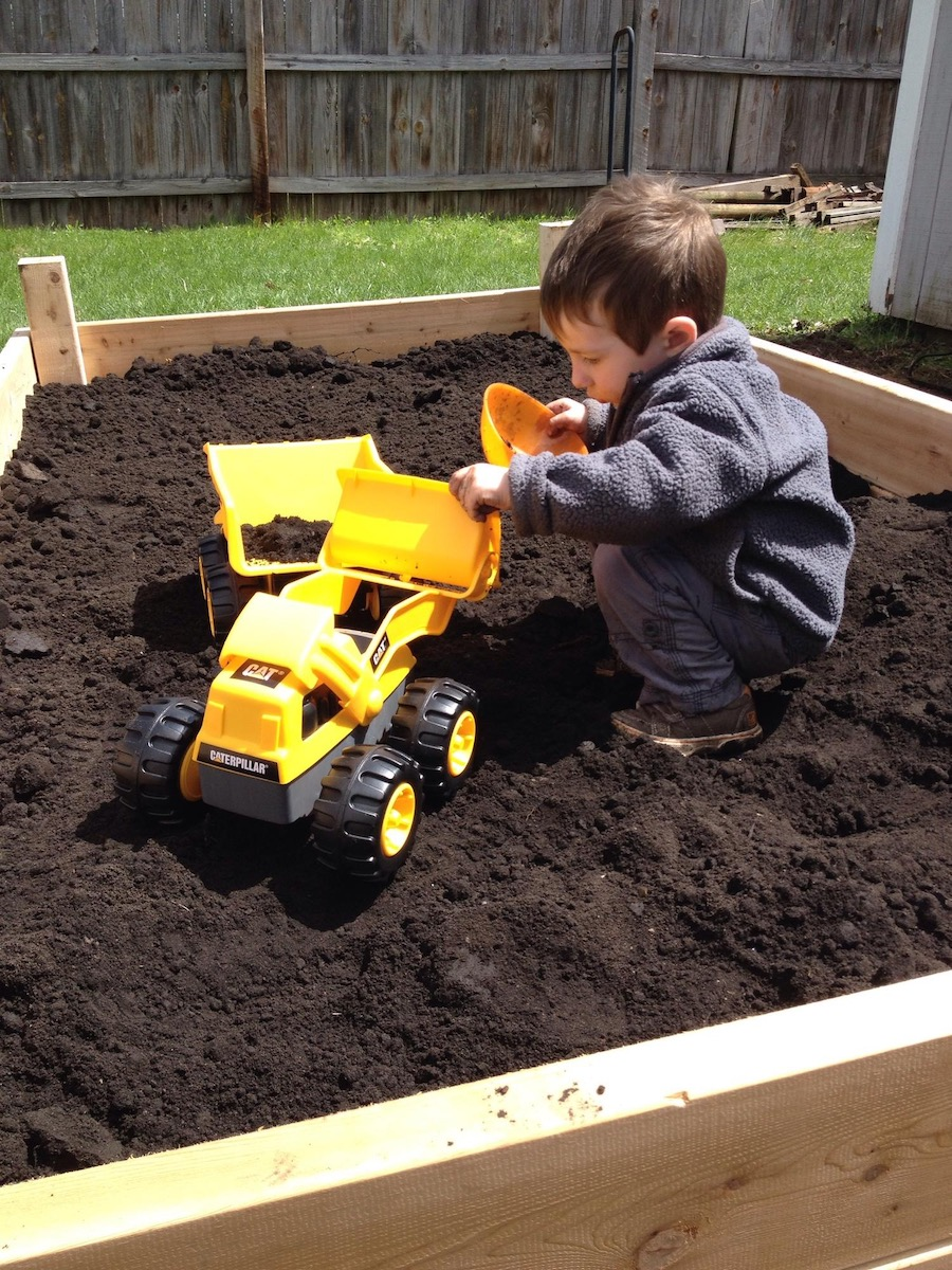 child digs in the raised garden bed with truck