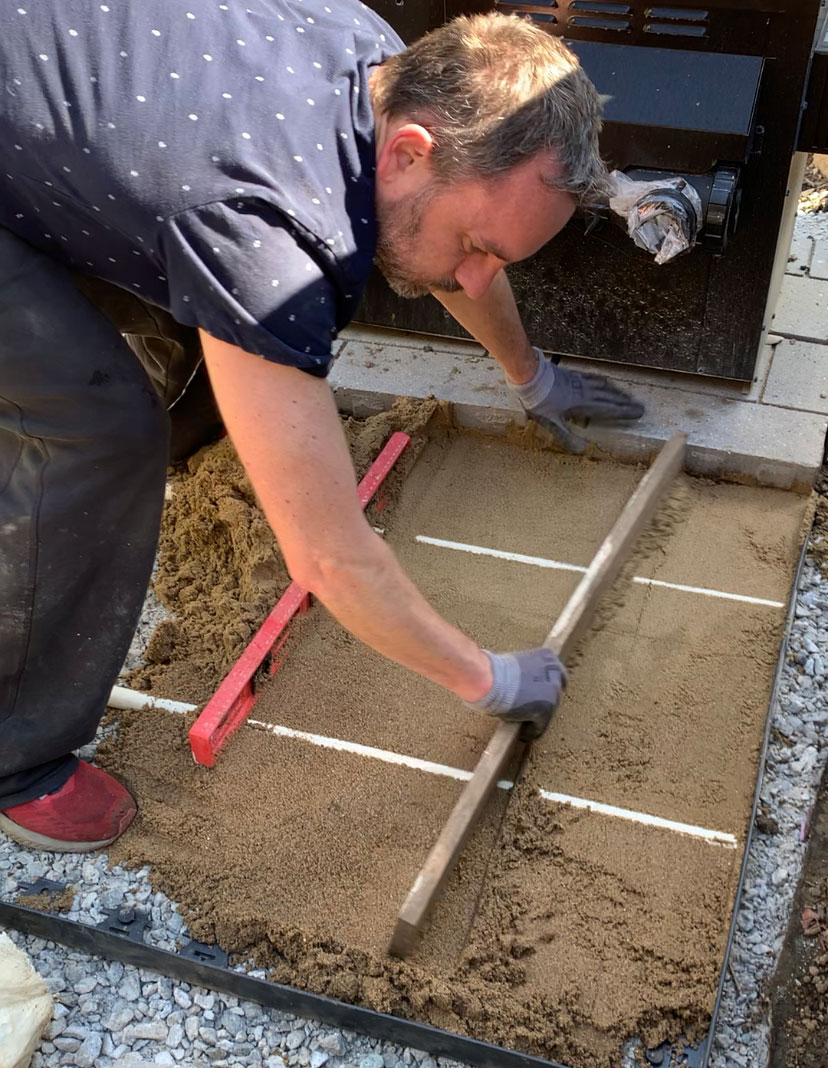 smoothing out leveling sand for paver landing