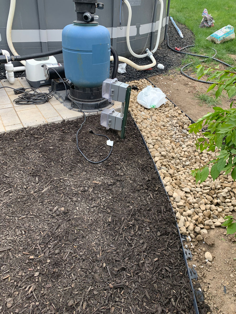 rock stream next to mulch by pool equipment