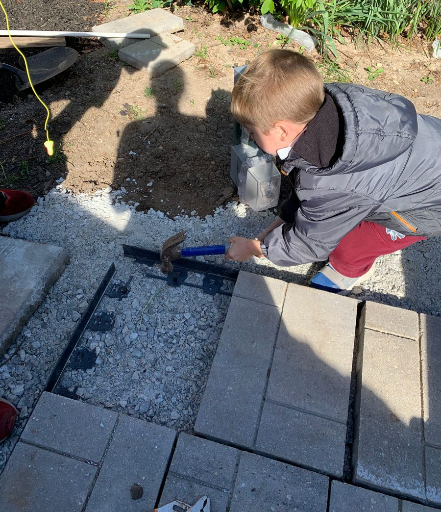 small boy hammering stakes into patio trim