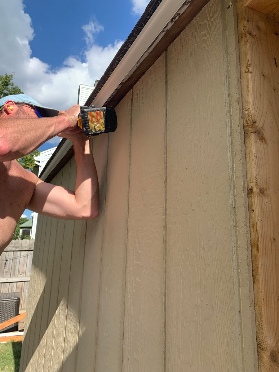 using drill to screw on new shed wall panels