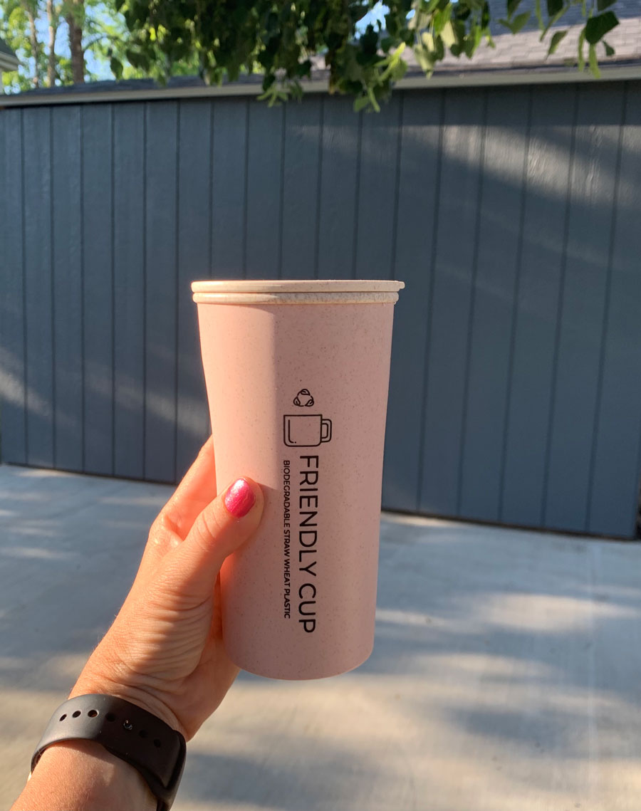 travel mug from friendly cup in front of gray painted shed