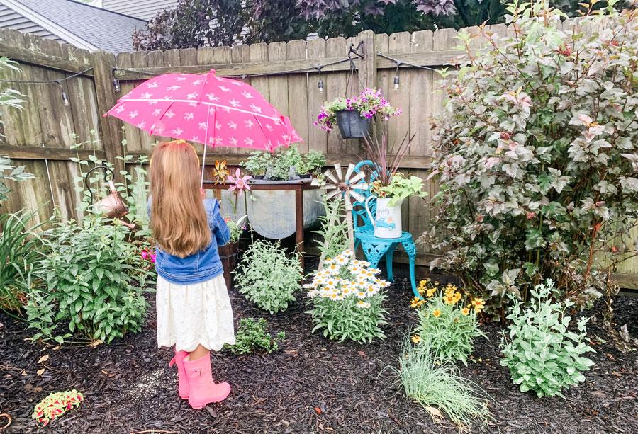 little girl with umbrella in wildflower garden
