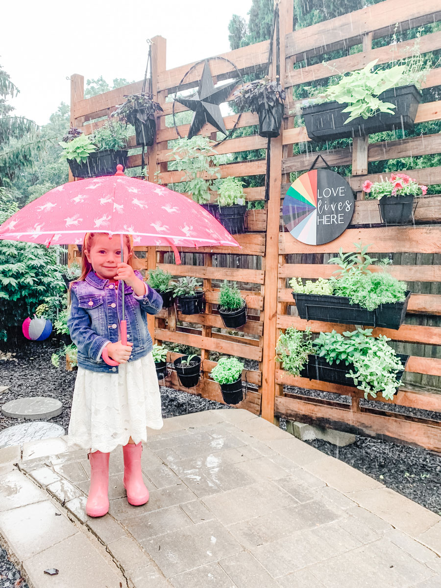 little girl with umbrella by vertical herb wall