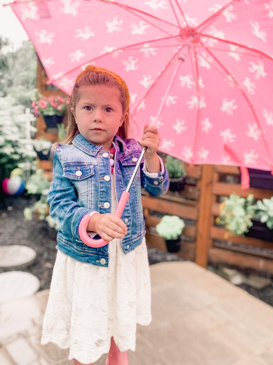 little girl under pink umbrella in backyard